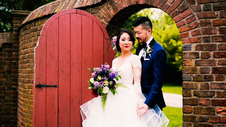 Bride and groom in front of a red gate at george weir barn wedding