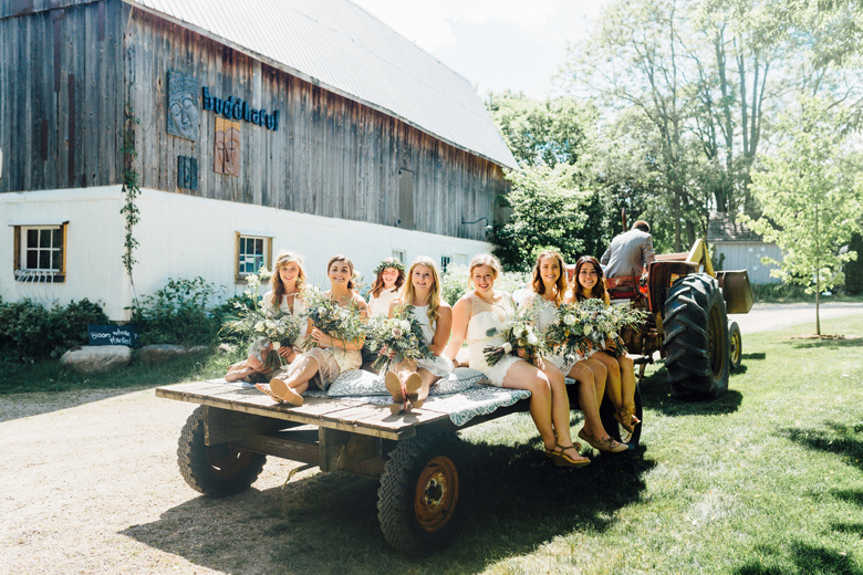 forest wedding bridesmaids riding tractor
