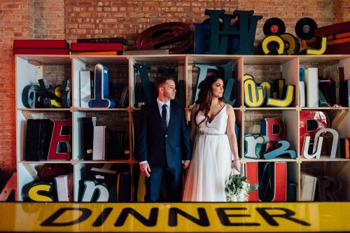 Salvage One Wedding Bride and Groom Posed Portrait near Dinner Sign